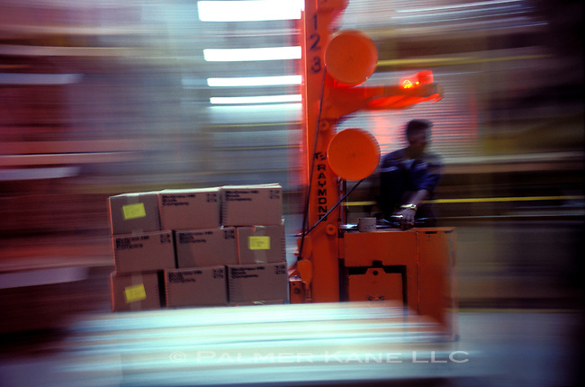 Man moving pallete of cartons on forklift in reverse, blurred background