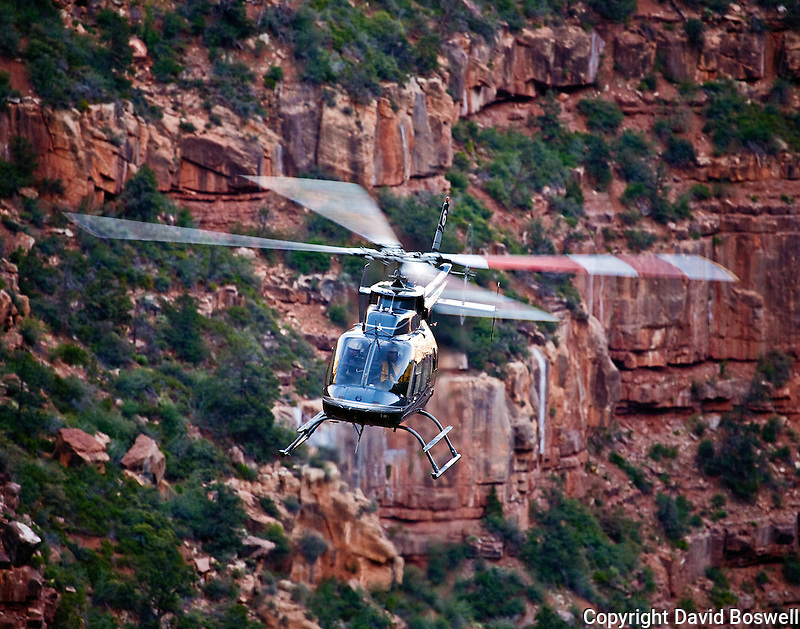 A helicopter flying below the North Rim of the Grand Canyon, near the North Kaibab Trail.