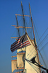 A view of an old sailboat masts and American flag flies against the blue sky.
