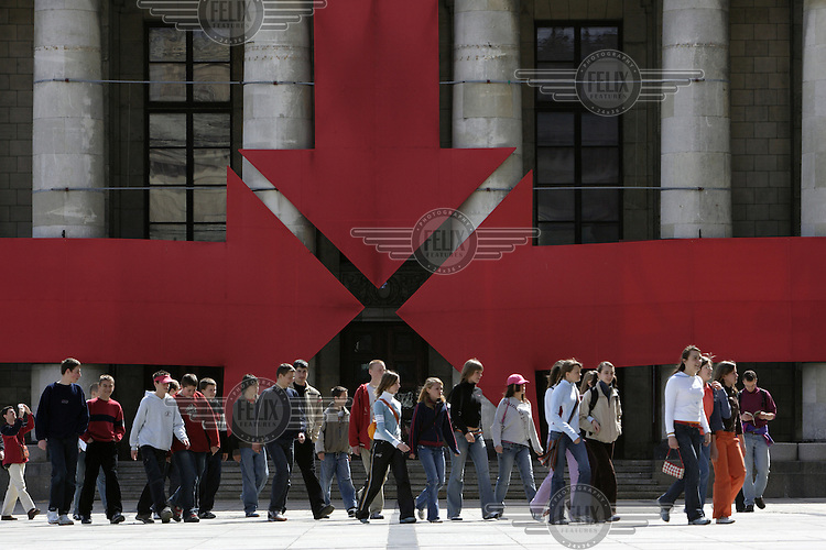 A group of schoolchildren on a school trip walk past a display of red converging arrows attached to the facade of the Soviet-built Palace of Culture.