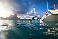 Woman diving off stern of catamaran in Bora Bora's lagoon