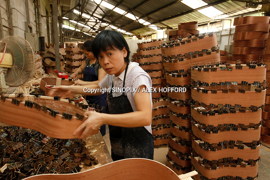 A worker makes a guitar at Australian guitar maker Bradley Clark's  factory in Bai Yun district, Guangzhou, Guangdong Province, China,  ..Photo by Alex Hofford / Sinopix.