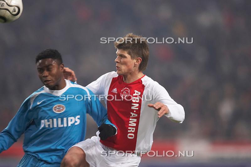 Nederland, Amsterdam, 11 maart 2006 .Eredivisie .Seizoen 2005-2006 .Ajax-PSV (0-0). .Profvoetballer Eric Addo (links) van PSV kopt de bal weg voordat Klaas Jan Huntelaar van Ajax erbij kan...