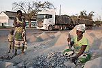 MUFULIRA, ZAMBIA- JULY 6: Women break stones along the road on July 6, 2016 in central Mufilira, Zambia. They sell it to people along the road. Glencore, an Anglo-Swiss multinational commodity trading and mining company, owns about 73 % of Mopani mines, which produces copper and some cobalt. The mine employs about 15,000 people. Many people in the area dependent of the mines and its subcontractors for work. (Photo by Per-Anders Pettersson)