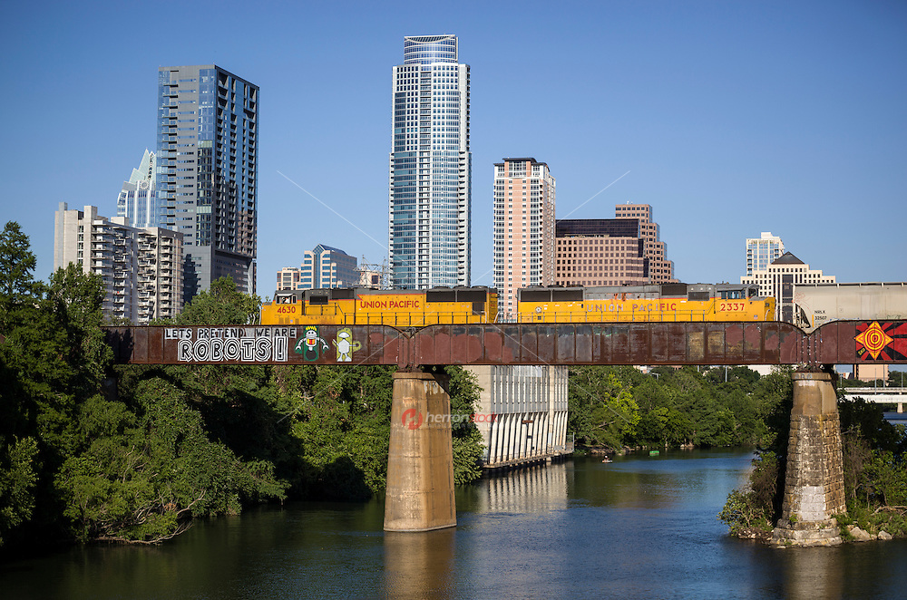 "Union Pacific Train passes over the ""Let's Pretend We're Robots,"" a famous and beloved inspirational graffiti painting on a the railroad bridge over Lady Bird Lake, overlooking the Austin skyline."