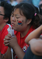 An South Korean National Soccer Team fan at the Fan Festival in downtown Leipzig, Germany is immersed in a prayer after South Korea falls behind France 1-0 in Korea's FIFA World Cup first round match against France, June 18, 2006. The game ended in a draw 1-1.