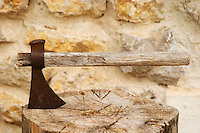 An old rusty axe with a wooden handle struck down in a chopped up piece of wood chopping board. Moulin Mas des Barres olive mill, Maussanes les Alpilles, Bouches du Rhone, Provence, France, Europe