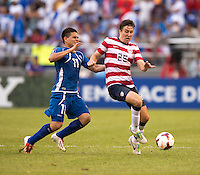 Matt Besler (25) of the United States holds off Rodolfo Zelaya (11) of El Salvador during the quarterfinals of the CONCACAF Gold Cup at M&T Bank Stadium in Baltimore, MD.  The United States defeated El Salvador, 5-1.