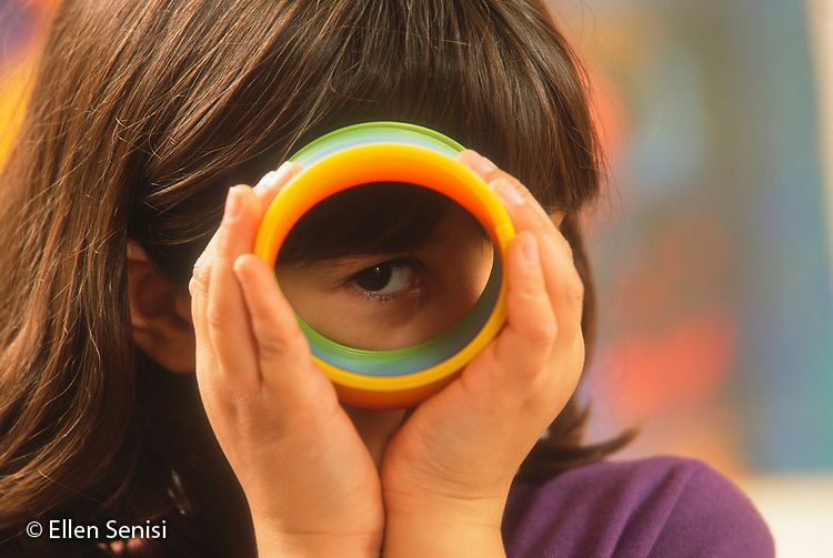 MR / Schenectady, NY. Yates Arts in Education Magnet Elementary School. Girl (7, Asian Indian-American & Caucasian, grade 2) looks through toy slinky with right eye. MR: Sin2. ID: AJ-LC. © Ellen B. Senisi