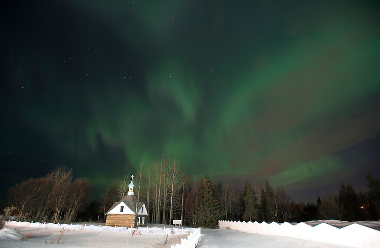 The aurora borealis dance in the sky above the Russian Orthodox Saint Nicholas Memorial Chapel in Kenai, Alaska. The bright green display of the northern lights at times filled the sky with green light.
