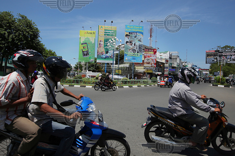 People ride on motorcycles on a new road linking Banda Aceh to the rest of Aceh Besar. Funded by the Multi Donor Fund, this road enables citizens to have easy access around Aceh and has brought new shops, business and housing to the area.