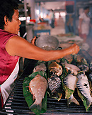 PERU, Amazon Rainforest, South America, Latin America, vendor grilling fishes on coal