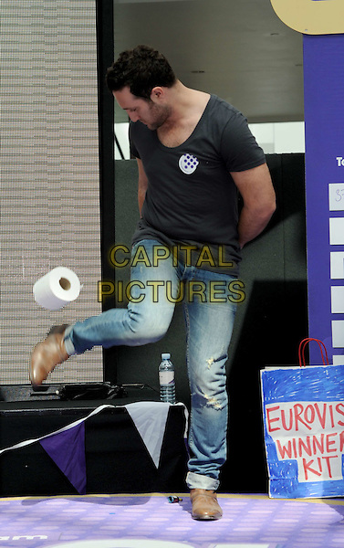 ANTONY COSTA of BLUE .Blue at the Cadburys Spots and Stripes Toilet Roll Challenge at Westfield Shopping Centre, London, England, UK,16th April 2011..full length black grey gray  t-shirt jeans kicking foot loo roll funny brown shoes .CAP/WIZ.© Wizard/Capital Pictures.