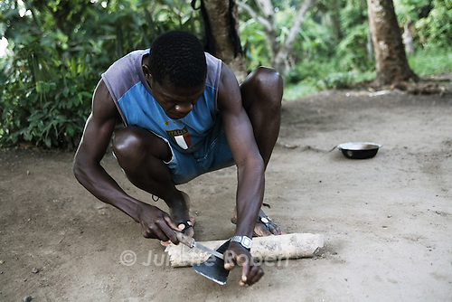 Stanley affute sa machette. Chaque jour, il tente de se faire embaucher dans les plantations voisines. Une semaine de débroussaillage lui permet d'acheter dix kilos de riz. Buutuo, Liberia, 2 avril 2011. Stanley sharpens his machette. Every day, he tries to get a job for the day in one of the neighbouring farms. One week of clearing in the bush earns him enough to buy 10kg of rice. Buutuo, Liberia, april 2nd 2011.