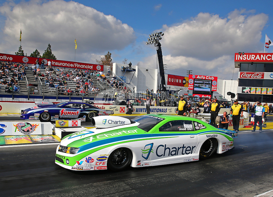 Feb 7, 2014; Pomona, CA, USA; NHRA top pro stock driver Shane Gray (near lane) races alongside Jason Line during qualifying for the Winternationals at Auto Club Raceway at Pomona. Mandatory Credit: Mark J. Rebilas-