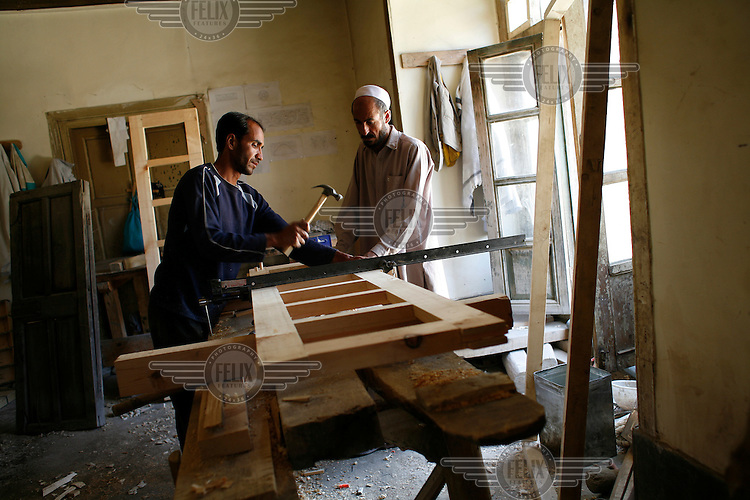 Carpenters in a workshop, making a window. Turquoise Mountain Foundation is working to preserve Afghanistan's traditional crafts and historical buildings. In Kabul, work has started in the historic Murad Khane part of Kabul, and is largely completed in the royal Kart-e-Parwan fort.