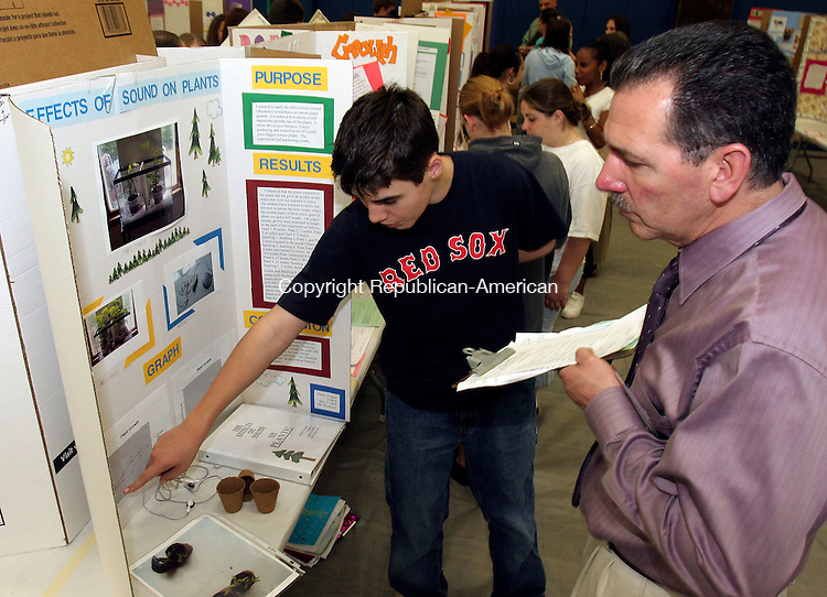 NAUGATUCK, CT-01 June 2006-060106TK01- (left to right) The City Hill Middle School in Naugatuck held its annual science fair Thursday. James Goggin details the work of his science project dealing with the effect of sound on plants to  John Olivieri, Science teacher. Olivieri participated as one of the judges in the science fair. Tom Kabelka Republican-American (City Hill Middle School, science fair, James Goggin, John Olivieri)
