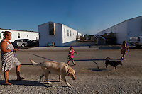 """Susan Bragole, Jayme Smith, and Jada Smith walk Bragole's dogs in the FEMA trailer park on Aug. 27, 2011 in Joplin, Mo. Smith was living in her grandmother's home when the May 22 tornado destroyed their house. Since the tornado, Smith has relocated to Baxter Springs with her sister and mother. Bragole remains in Joplin. """"When the tornado hit, it separated everybody,"""" Bragole said."""