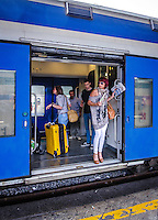 Urban Street Photography, in Termini station, Rome. The hustle and bustle of this busy train station is revealed by the vibrant colours of the train, the luggage, and the people preparing for their journey.