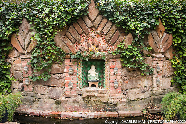 A small shrine constructed of bricks and stones and  adorned with marbles is one of many playful pieces of garden art in the Douglas Chandor Garden in Weatherford, Texas.