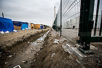 Separation between the &quot;old camp&quot; (on the left) and the containers' &quot;new camp&quot; protected by high fences, security guards and finger prints reader at the gate used as the &quot;key&quot; to enter.<br /> <br /> Calais Jungle Camp.<br /> <br /> Under the Sky of Calais &amp; Dunkirk. Two Camps, Two Sides of the Same Coin: Not 'migrants', Not 'refugees', just Humans.<br /> <br /> France, 24-30/03/2016. Documenting (and following) Zekra and her experience in the two French camps at the gate of the United Kingdom: Calais' &quot;Jungle&quot; and Dunkirk's &quot;Grande-Synthe&quot;. Zekra lives in London but she is originally from Basra in Iraq. Zekra and her family had to flee Kuwait - where they moved for working reason - due to the &quot;Gulf War&quot;, and to the Western Countries' will to &quot;export Democracy in Iraq&quot;. Zekra is a self-motivated volunteer and founder of &quot;Happy Ravers&quot;, a group of people (not a NGO or a charity) linked to each other because of their love for rave parties but also men and women who meet up every week to help homeless people and other people in need in Central London. (Here there are some of the stories I covered about Zekra and &quot;Happy Ravers&quot;: http://bit.ly/1XVj1Cg &amp; http://bit.ly/24kcGQz &amp; http://bit.ly/1TY0dPO). Zekra worked as an English teacher in the adult school at Dunkirk's &quot;Grande-Synthe&quot; camp and as a cultural mediator and Arabic translator for two medic teams in Calais' &quot;Jungle&quot;. Please read her story at the beginning of this reportage.