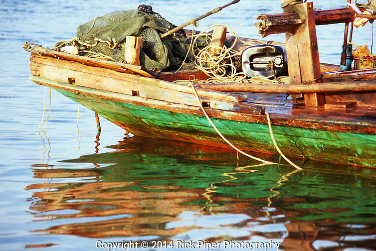 Colourful reflections of traditional Cham fishing boat stern reflected in ripples on the Sanke river at dawn, Kampot, Cambodia
