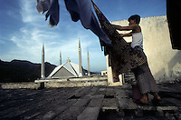 A man hangs laundry across from the Faisal Mosque in Islamabad. The largest mosque in Pakistan, the Faisal Mosque is the fourth largest mosque in the world and was ompleted in 1986. It was designed to resemble a Bedouin's tent. (1996)