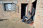 Dominik Tengani gets help with his wheelchair from his son Donald in his home in Kuwadzana, Zimbabwe. Tengani is vice chair of the Spinal Injuries Association of Zimbabwe, which supports and advocates for the rights of people living with spinal injuries. He says doctors have been unable to diagnose the cause of his medical condition. He uses an appropriately-designed and fitted wheelchair provided by the Jairos Jiri Association with support from CBM-US.