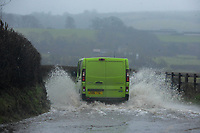 A van passes through flood water on Culfor Road in Loughor, Swansea.