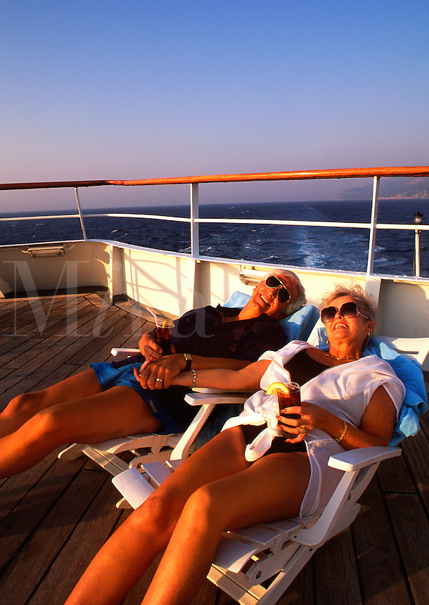 Retired couple lounging in deck chairs on cruise ship