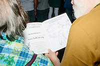 People look at a campaign coloring book before Texas senator and Republican presidential candidate Ted Cruz speaks to a crowd at the kick-off event at his New Hampshire campaign headquarters in Manchester, New Hampshire.
