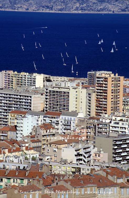 Waterfront high-rise buildings and sailboats in the harbour, Marseille, France.