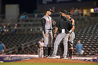 Arkansas Travelers pitching coach Pete Woodworth (32) visits the mound with pitcher Wyatt Mills (41) and catcher Joe DeCarlo (7) during a Texas League game between the Northwest Arkansas Naturals and the Arkansas Travelers on May 30, 2019 at Arvest Ballpark in Springdale, Arkansas. (Jason Ivester/Four Seam Images)