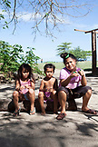 FRENCH POLYNESIA, Moorea. Portrait of local kids sitting on the side of a road in Moorea Island.