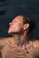 Young man floating in water, eyes shut, elevated view