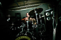 A punk rock drummer plays in a concert in the basement of the White House in Woodstock, Illinois.  The White House was a small suburban residential home rented by a group of 20-somethings in Woodstock, Illinois, a distant northwestern suburb of Chicago.  For about a year, the renters of the house staged punk-rock concerts in the house's small basement, without the approval of the neighborhood, local government, or police.  .