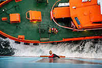 After navigating the Mary Maersk, the largest container ship in the world, from the port at Gothenburg to the open sea, the local pilot prepares to climb down the ship's ladder to a waiting boat. Often the pilots will be picked up by helicopter, especially in rough seas.