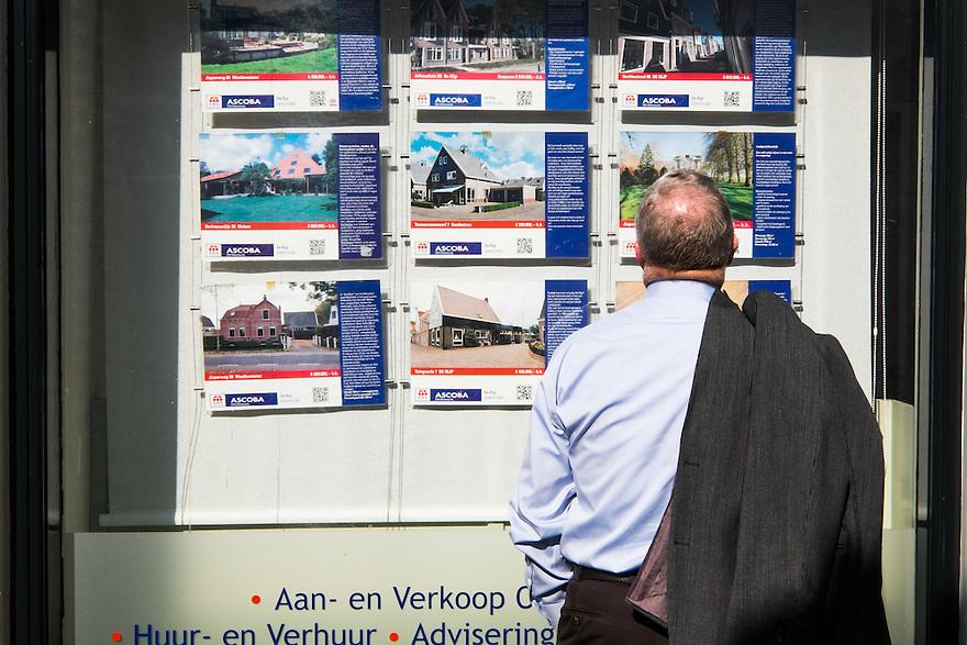 Nederland, Alkmaar, 17 maart 2015<br /> De Rijp, zeer mooi dorpje behorend tot de gemeente Alkmaar. Man kijkt in de etalage van een makelaar<br /> <br /> Foto: (c) Michiel Wijnbergh