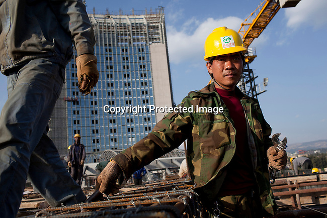 ADDIS ABABA, ETHIOPIA - NOVEMBER 17: Chinese construction workers build the new African Union Buildings on November 17, 2010 in Addis Ababa, Ethiopia. The building is built for free. Chinese companies are investing and working all over Africa and in Ethiopia they are mainly occupied with infrastructure projects around the country. Photo by Per-Anders Pettersson.