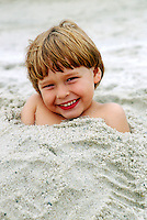 Young boy burriend in the sand. Cape Cod