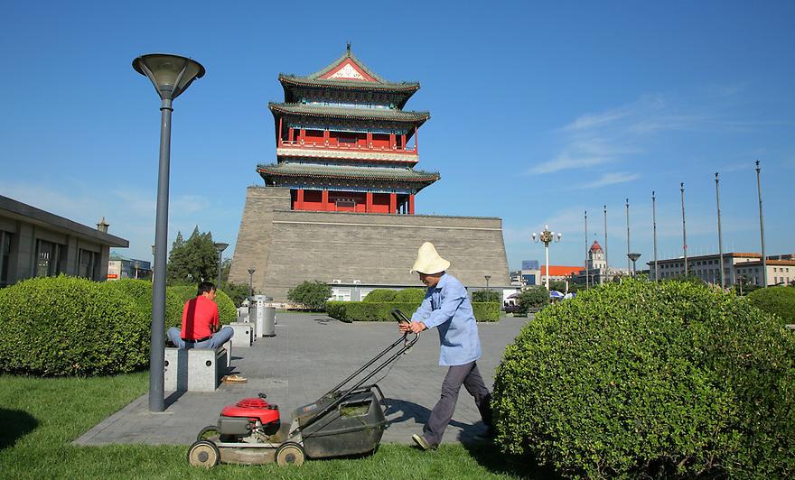 Gardener mowing lawn. Front Gate Tiananmen Square. Beijing China