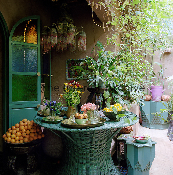 A group of green-painted tables occupies an inner courtyard beyond the kitchen door