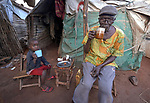 Dominic Du drinks tea with his grandson, 6-year old Josef Philip, in front of their shelter in a displaced persons camp at the Holy Family Catholic Church in Wau, South Sudan. The church has provided food, shelter material, and health care, and the presence of clergy and religious has fostered a sense of relative safety for the families who first occupied the church grounds when fighting enveloped the city in 2016.