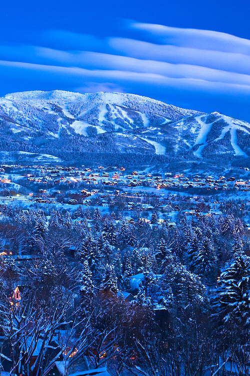 The lights of old town Steamboat Springs, Colorado glow at dusk below the majestic Mt. Werner.