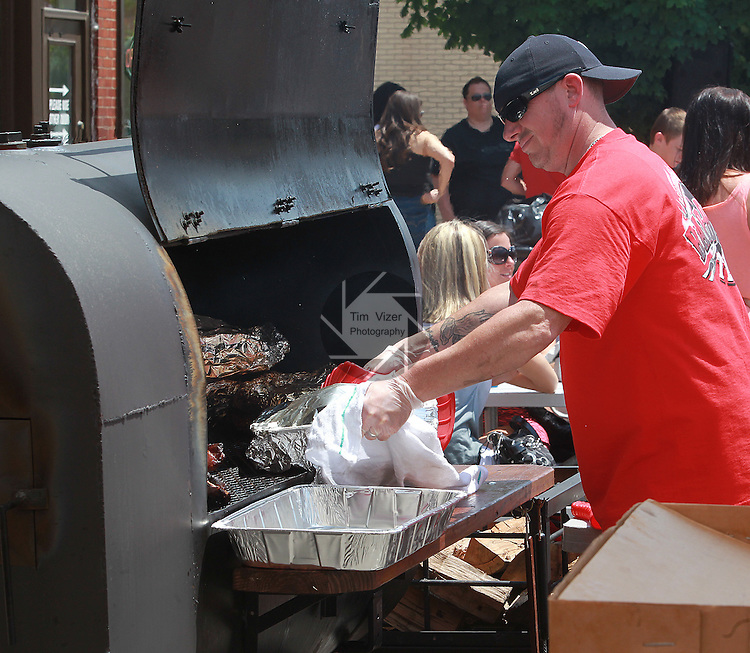 Belleville Fire Department pipeman Ray Winchester removes a pan of ribs from a smoker at the first Belleville Brew & Que in downtown Belleville, which was set up in the third block of East Main Street.  This first-ever event featured a Barbecue Challenge and craft beer tasting at 20 downtown businesses. Three bands played during the event, which ran from 11 a.m. to 9 p.m.  The Craft Beer Walk ran from noon to 4 p.m. at select downtown Belleville merchants.  For a $15 ticket, you could have 16 tastings of a wide variety of craft beers.  The Barbecue Challenge ran all day, with vendors selling samples of two meats for $1, or a meaty rib bone for $2.