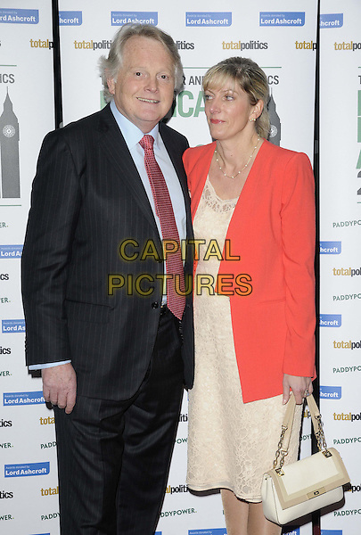 Lord Michael Dobbs & guest.The Paddy Power & Total Politics Political Book Awards 2013, BFI Imax, Charlie Chaplin Walk, London, England..February 6th, 2013.half length black suit blue shirt red tie salmon coral blazer white cream dress .CAP/CAN.©Can Nguyen/Capital Pictures.