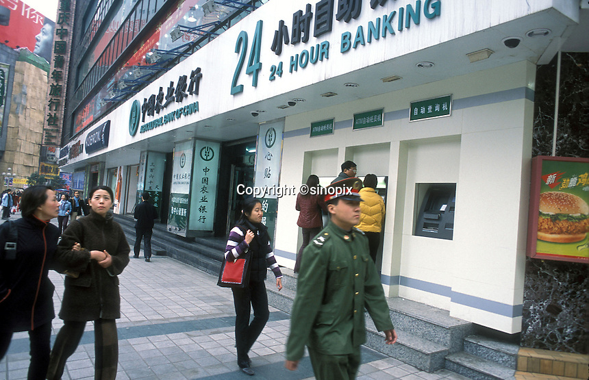 PLA officer walks pass the Agricultural Bank of China which provides 24 hours banking service in Chongqing, China..
