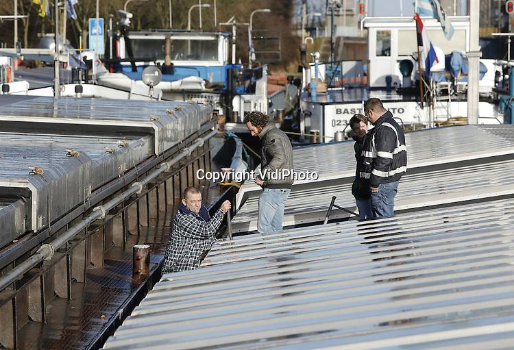 Foto: VidiPhoto<br /> <br /> WEURT - Binnenvaartschippers op het Maas-Waal kanaal bij Weurt (Nijmegen) maken woensdag van de nood een deugd met extra onderhoud van hun vrachtschepen. Zo'n 25 schippers zijn noodgedwongen werkloos omdat vanwege de stukgevaren stuw bij Grave, ook de sluis bij Weurt niet open mag. Daarmee zou het waterpeil tussen de Maas en de Waal nog verder zakken, met als gevolg grote schade aan de woonboten. Een ongeluk komt zelden alleen, want ook het waterpeil in de Waal is ongebruikelijk laag omdat er al weken geen regen van betekenis is gevallen. Op het Maas-Waal kanaal is het water 1.20 meter gezakt. De schippers voor de sluis bij Weurt liggen daardoor 'gevangen' tussen de Waal en de noodstuw bij Heumen. Binnenvaartschipper Mark Peters (53, foto) van de 84 meter lange Dusky uit Angeren ligt al sinds vorige week donderdag stil met een lading kunstmest voor boeren in Zuid-Duitsland. Ook het transport van diervoeders van de Rotterdamse haven naar Duitsland loopt grote vertraging op. Zijn schade bedraagt rond de 1350 euro per dag.