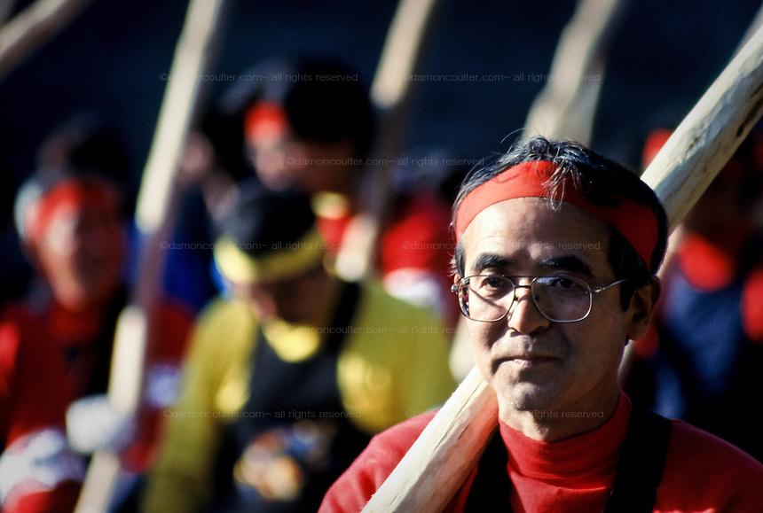A man wears red as he carries a rough wooden pole to help guide a large tree trunk to a shrine during the Onbashira festival that takes place every seven years in Suwa, Nagano Japan. 2003