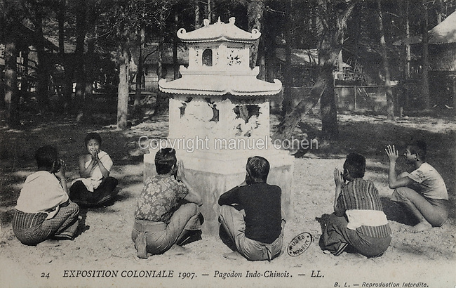 Indochinese pagoda surrounded by Laotian worshippers in the Indochinese Village (French Indochina was a colony 1887-1954), at the Colonial Exhibition of 1907, held in the Jardin d'Agronomie Tropicale, or Garden of Tropical Agronomy, in the Bois de Vincennes in the 12th arrondissement of Paris, postcard from the nearby Musee de Nogent sur Marne, France. The garden was first established in 1899 to conduct agronomical experiments on plants of French colonies. In 1907 it was the site of the Colonial Exhibition and many pavilions were built or relocated here. The garden has since become neglected and many structures overgrown, damaged or destroyed, with most of the tropical vegetation disappeared. The site is listed as a historic monument. Picture by Manuel Cohen / Musee de Nogent sur Marne